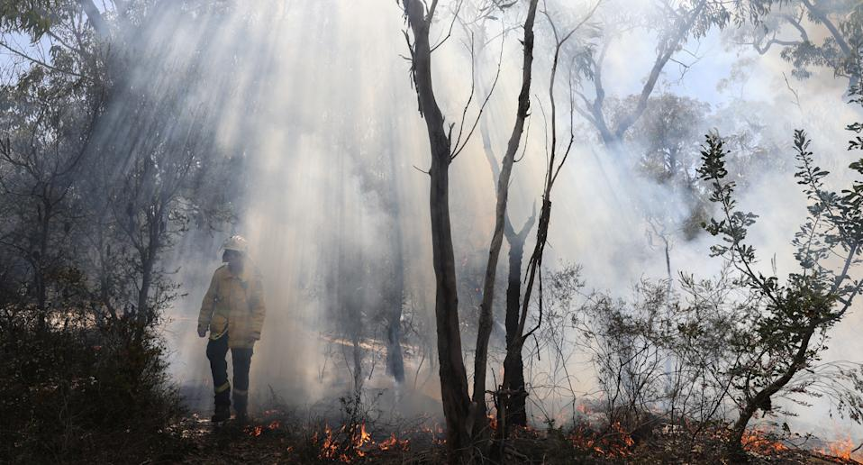 Firefighter emerging from smouldering fire.