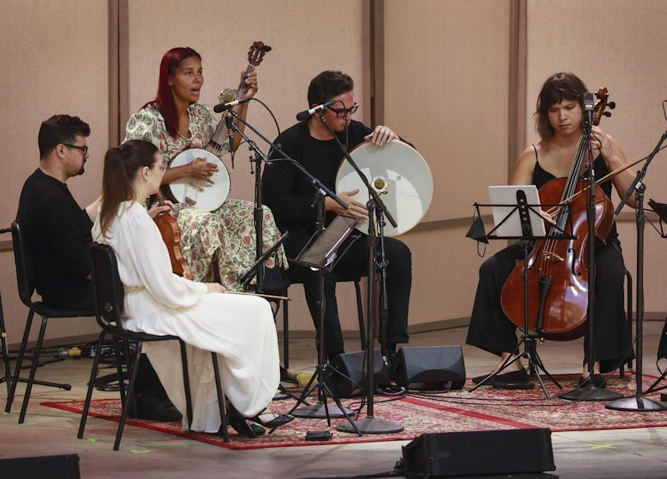 Five people play instruments, including a cello and banjo
