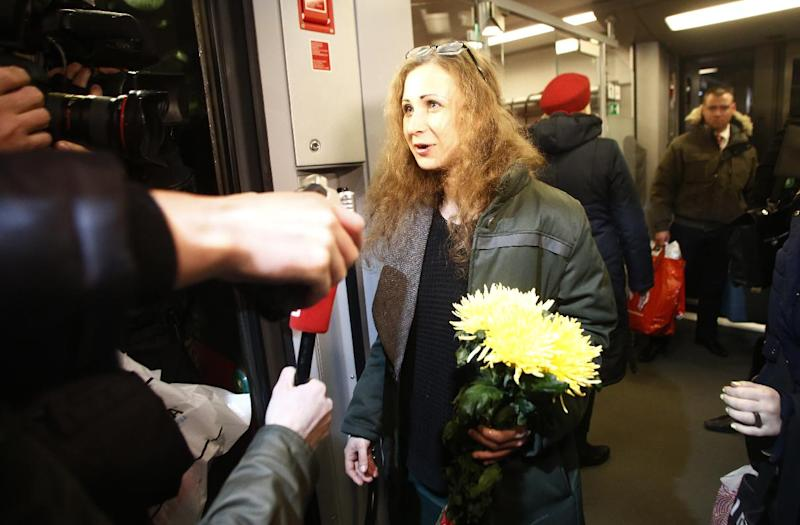 Member of Russian punk band Pussy Riot, Maria Alekhina, speaks to the media while leaving a train upon her arrival in Moscow, Russia, late Monday, Dec. 23, 2013. Two jailed Pussy Riot members, Alekhina and Nadezhda Tolokonnikova, were released following an amnesty law that both described as a Kremlin public relations stunt ahead of the Winter Olympics. (AP Photo/Denis Tyrin)