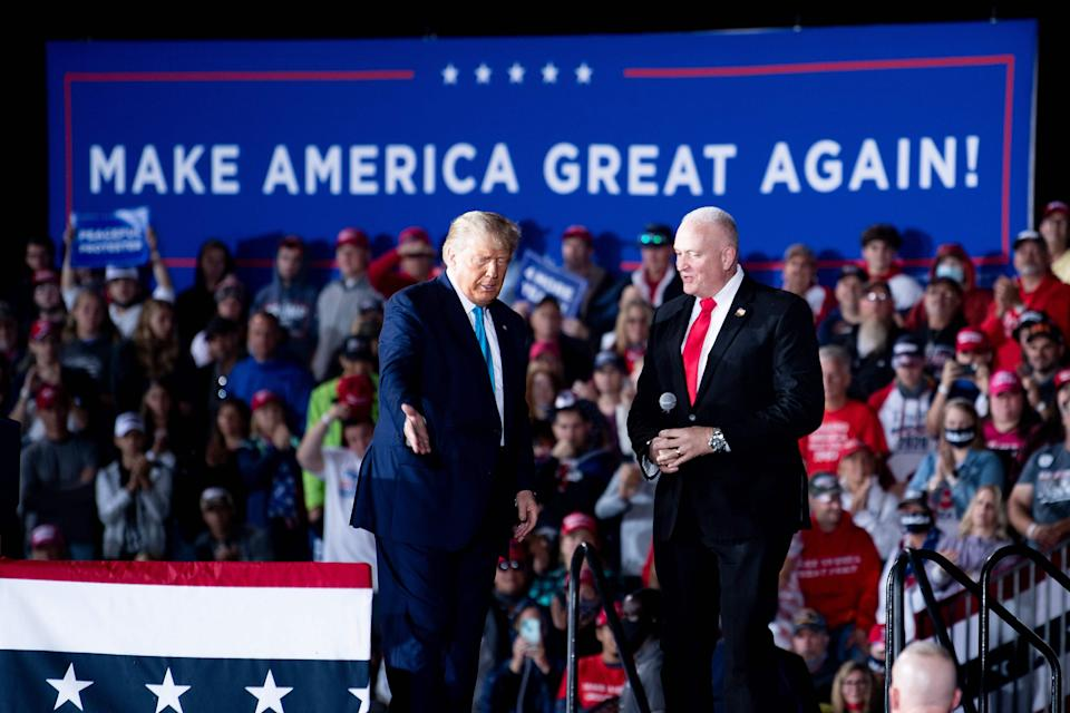 """US President Donald Trump and National President of the Fraternal Order of Police Patrick Yoes speak during a """"Make America Great Again"""" campaign rally at Harrisburg international airport in Middletown, Pennsylvania."""