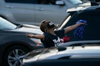 A woman stretches while waiting to hear Kamala Harris during a drive-in event in Atlanta, Georgia