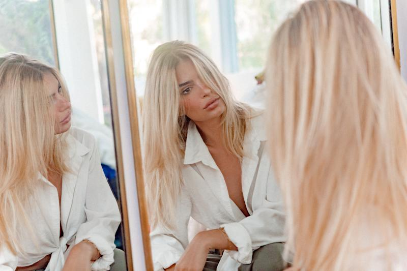 Emily Ratajkowsk with blonde hair looking in the mirror