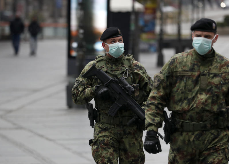 In this March 26, 2020, photo, Serbian army soldiers patrol in Belgrade's main pedestrian street, in Serbia. Since declaring nationwide state of emergency Serbian President Aleksandar Vucic has suspended parliament, giving him widespread powers such as closing borders and introducing a 12-hour curfew. (AP Photo/Darko Vojinovic)