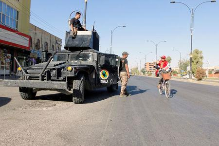 A cyclist gestures at Iraqi security forces, on a street of Kirkuk, Iraq October 19, 2017. REUTERS/Ako Rasheed - RC1433BB18F0