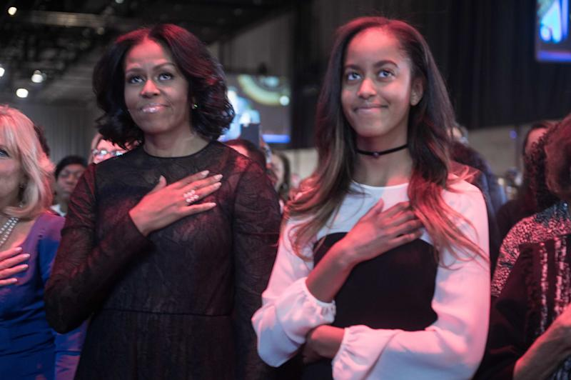 First lady Michelle Obama (left) and daughter Malia listen to the national anthem before President Barack Obama delivers his farewell address on Jan. 10, 2017.
