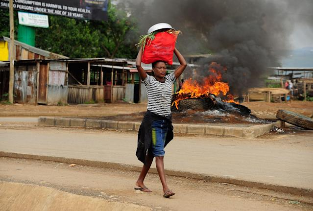 <p>A woman walks with a bag on her ahed as supporters of National Super Alliance (NASA) presidential candidate Odinga barricade roads and burn tyres as they demonstrate in the streets on the boycott of the upcoming elections on Oct. 24, 2017 in Kisumu, Kenya. (Photo: Kevin Midigo/AFP/Getty Images) </p>