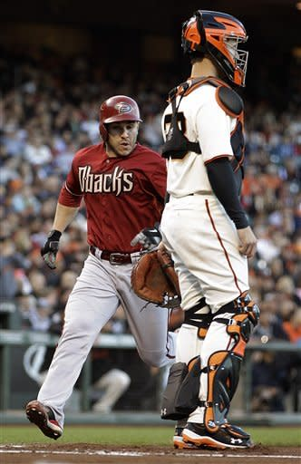 Arizona Diamondbacks' Miguel Montero, left, scores behind San Francisco Giants catcher Buster Posey in the second inning of a baseball game on Wednesday, May 30, 2012, in San Francisco. Montero scored on a sacrifice fly hit by Arizona's Ryan Roberts. (AP Photo/Ben Margot)