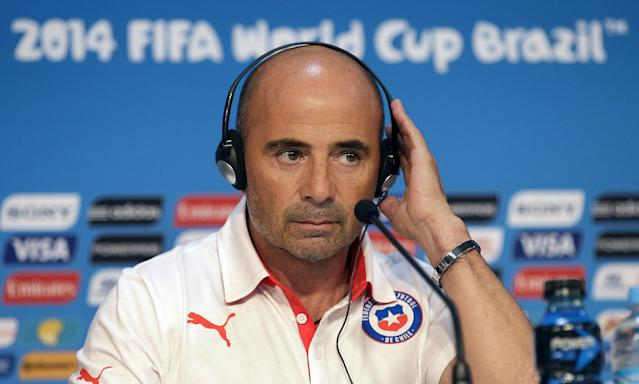 Chile's head coach Jorge Sampaoli holds his translator headphone during a press conference the day before the group B World Cup soccer match between Chile and Australia in the Arena Pantanal in Cuiaba, Brazil, Thursday, June 12, 2014. (AP Photo/Michael Sohn)