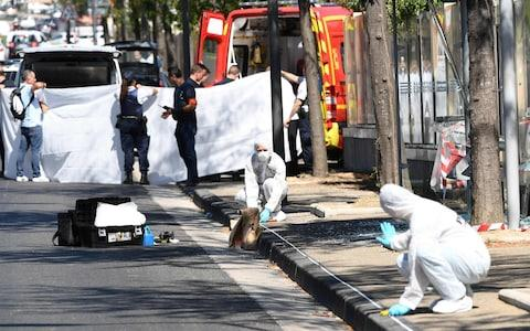 A white sheet is erected as a body of a victim is evacuated to a waiting ambulance while French forensic police officer search the crash site in Marseille - Credit: BORIS HORVAT/AFP