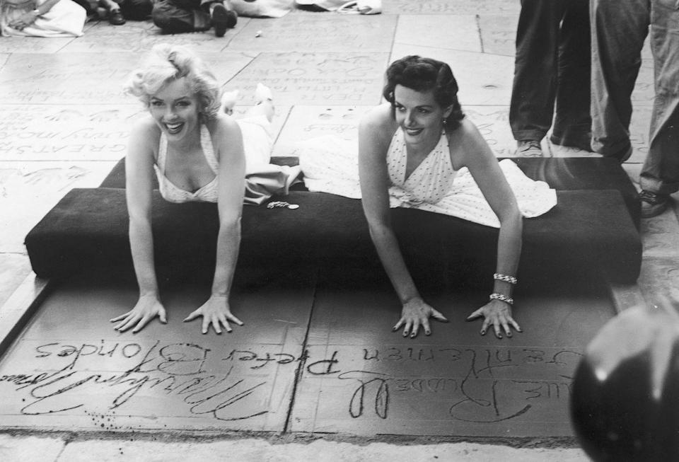 <p>Marilyn left her hand and footprints in the cement at Grauman's Chinese Theater in Los Angeles. She's accompanied by Jane Russell, her co-star in <em>Gentlemen Prefer Blondes</em>.</p>