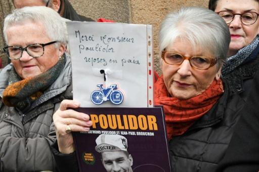 "A mourner holds a sign reading ""Thank you Mr Poulidor, rest in peace"" at the funeral of French cyclist Raymond Poulidor"