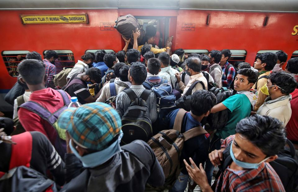 Migrant workers and their families board an overcrowded passenger train, after government imposed restrictions on public gatherings in attempts to prevent spread of coronavirus disease (COVID-19), in Mumbai, India, March 21, 2020. REUTERS/Prashant Waydande