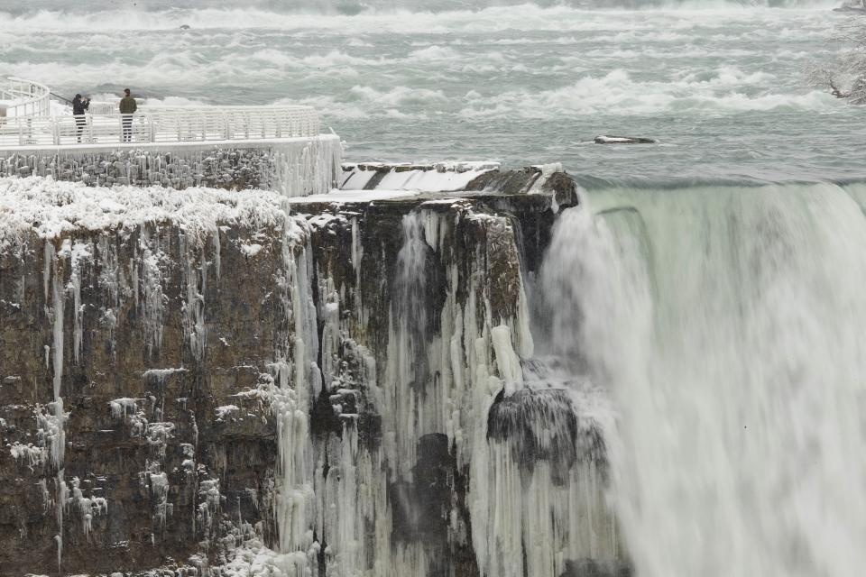 TOPSHOT - A person has their photo taken on the US side of the Horseshoe Falls in Niagara Falls, New York, on January 27, 2021, as taken taken from the Canadian side. (Photo by Geoff Robins / AFP) (Photo by GEOFF ROBINS/AFP via Getty Images)