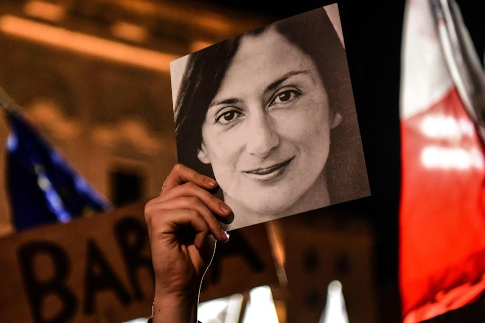A person holds a photo of the killed journalist Daphne Caruana Galizia, during a protest in 2019 in Valletta (AFP via Getty Images)