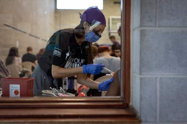 Health-care workers with Humber River Hospital administer doses of the Moderna COVID-19 vaccine at a temporary clinic for members of Toronto's Spanish-speaking community at the Glen Long Community Centre on May 14, 2021. (Evan Mitsui/CBC - image credit)
