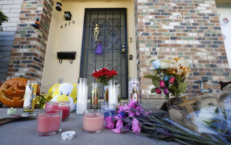 A makeshift memorial has been set up in front of the Moore home on Monday Oct. 28, 2013, in Phoenix, to remember the four shooting victims. Police say loud barking dogs might have led to 56-year-old Michael Guzzo, to kill four of his neighbors and the neighbors' two dogs before turning the gun on himself, and dying. The victims were identified as Bruce Moore, 66; his daughter, Renee Moore, 36; her husband, Michael Moore, 42, who took his wife's name; and Renee's son, Shannon Moore, 17. (AP Photo/Ross D. Franklin)