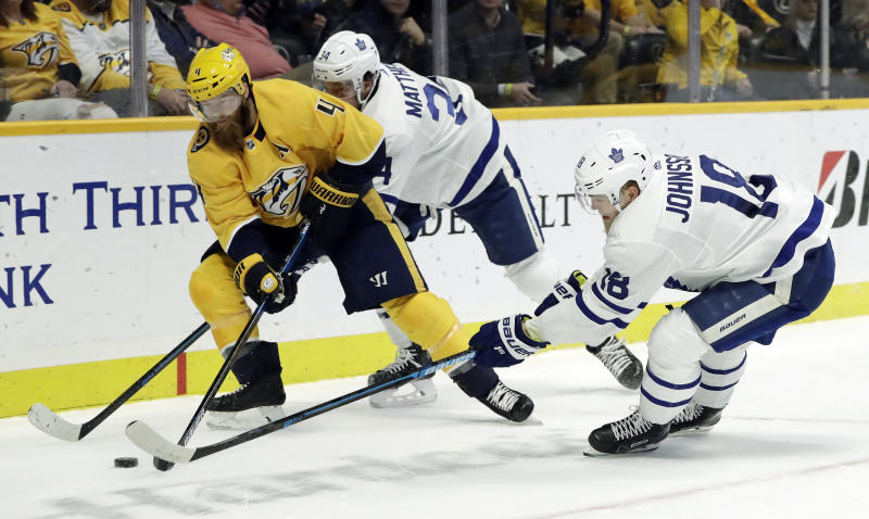Nashville Predators defenseman Ryan Ellis (4) passes the puck away from Toronto Maple Leafs center Auston Matthews (34) and left wing Andreas Johnsson (18), of Sweden, in the first period of an NHL hockey game Tuesday, March 19, 2019, in Nashville, Tenn. (AP Photo/Mark Humphrey)
