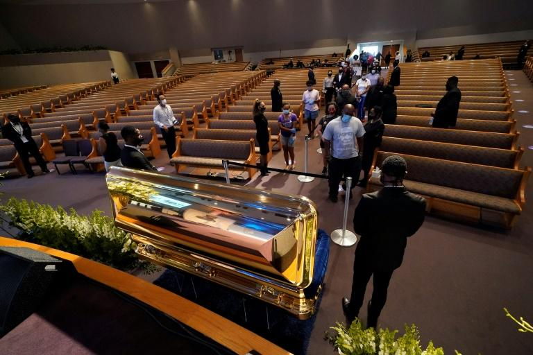 Mourners pass by the open casket of George Floyd -- because of the coronavirus pandemic, all mourners were required to wear masks and only pause briefly at the coffin (AFP Photo/David J. Phillip)