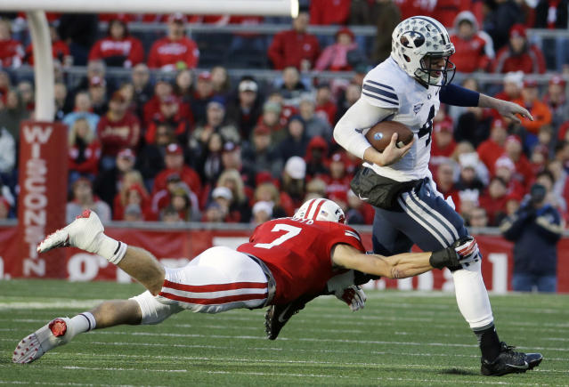 Brigham Young's Taysom Hill, right, tries to break away from Wisconsin's Michael Caputo during the first half of an NCAA college football game on Saturday, Nov. 9, 2013, in Madison, Wis. (AP Photo/Morry Gash)