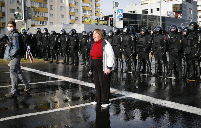 A protester shouts in front of a riot police line during a rally in Minsk, Belarus, Sunday, Oct. 4, 2020. Hundreds of thousands of Belarusians have been protesting daily since the Aug. 9 presidential election. (AP Photo)