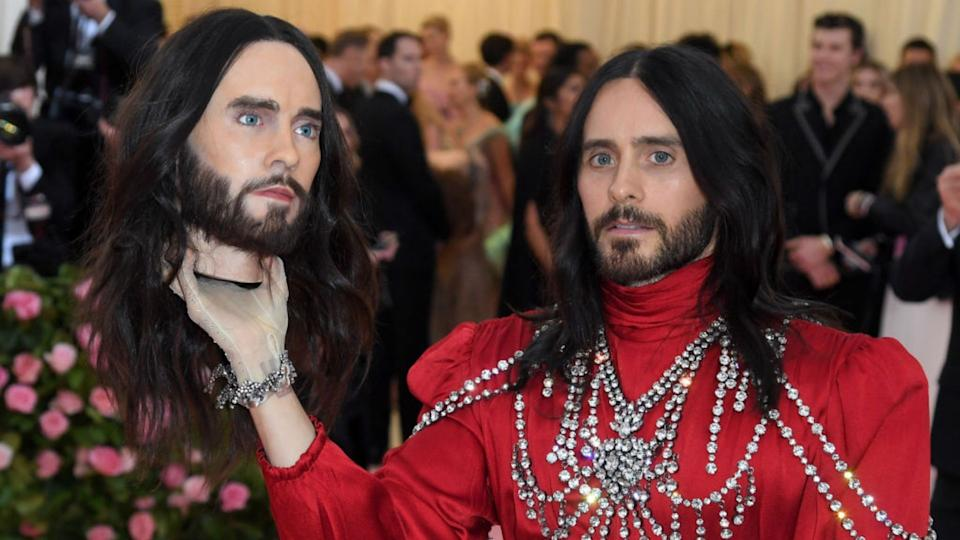 Jared Leto wearing red bedazzled suit poses with his own head at Met Gala.