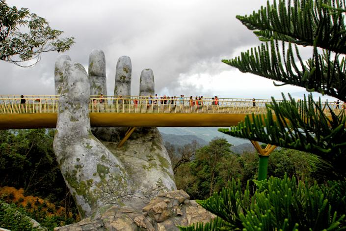 Nestled in the forested hills of central Vietnam, two giant concrete hands emerge from the trees, holding up a glimmering golden bridge crowded with gleeful visitors taking selfies at the country's latest eccentric tourist draw.
