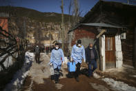 Dr. Yasin Kaya, center and health worker Yusuf Duran, left, members of the the Koyulhisar Public Health Center vaccination team, walk to vaccinate 85-year-old Ibrahim Yigit at his house in the isolated village of Gumuslu in the district of Sivas, central Turkey, Friday, Feb. 26, 2021. (AP Photo/Emrah Gurel)