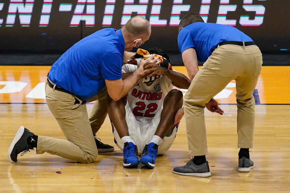 Florida guard Tyree Appleby (22) is treated after being injured in the second half of a first round game against Virginia Tech in the NCAA men's college basketball tournament at Hinkle Fieldhouse in Indianapolis, Friday, March 19, 2021. (AP Photo/Michael Conroy)