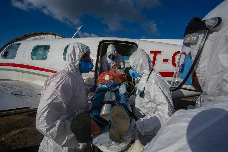 Brazilian COVID-19 positive patient Edinilson Silva, 47, is taken out of plane, which is equipped as an ICU unit, upon arrival to the city of Santarem, Para state, Brazil, on July 15, 2020. - Silva was transferred from the municipality of Almeirim. (Photo by TARSO SARRAF / AFP) (Photo by TARSO SARRAF/AFP via Getty Images)