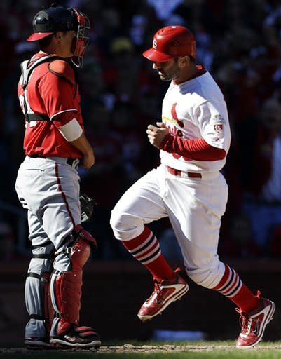 St. Louis Cardinals' Daniel Descalso, right, scores on a sacrifice fly by Jon Jay as Washington Nationals catcher Kurt Suzuki, left, stands by during the second inning in Game 1 of baseball's National League division series, Sunday, Oct. 7, 2012, in St. Louis. (AP Photo/Jeff Roberson)
