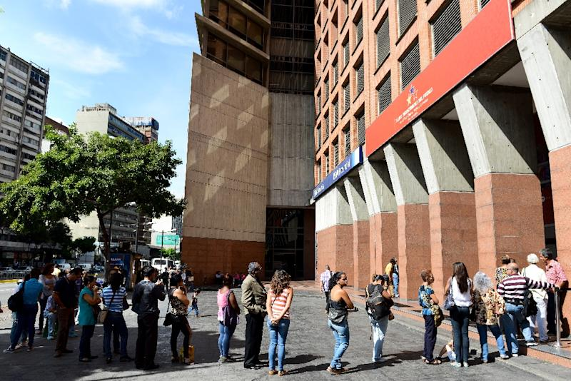 """People queue to withdraw money from an ATM in Caracas on November 14, 2017, as Venezuela and PDVSA were declared by ratings agencies to be in """"selective default"""""""