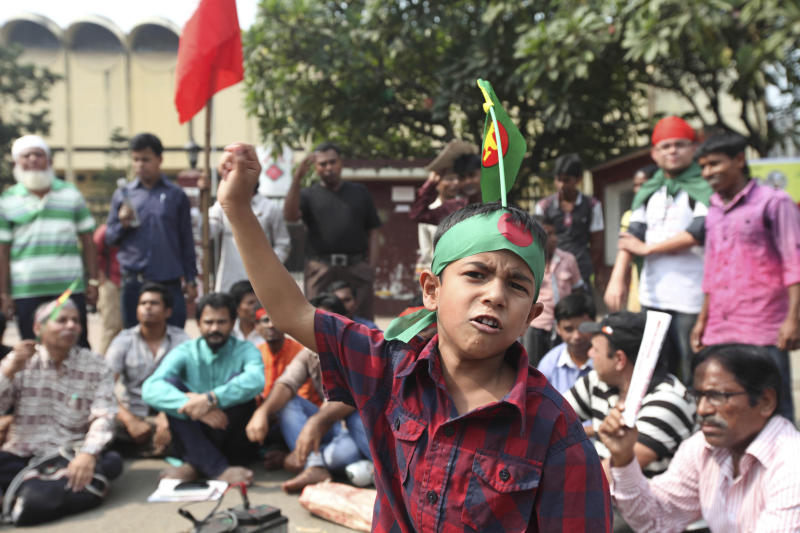 A Bangladeshi boy shouts slogans as he joins a rally with activists demanding maximum penalty for war criminals in Dhaka, Bangladesh, Sunday, Nov. 3, 2013. A special war crimes tribunal in Bangladesh on Sunday sentenced to death two Bangladeshis now living in the U.S. and Britain for crimes against humanity during the country's independence war against Pakistan in 1971. (AP Photo/Suvra Kanti Das)