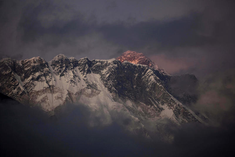 FILE - In this Oct. 27, 2011 file photo, the last light of the day sets on Mount Everest as it rises behind Mount Nuptse as seen from Tengboche, in the Himalaya's Khumbu region, Nepal. Guy Cotter was so concerned about the safety of Sherpa guides and porters through Mount Everest's notorious Khumbu Icefall that he and another commercial guide operator hatched a plan: Before this year's climbing season began, they would use helicopters to transport four tons of equipment above the icefall. Nepal-based Simrik Air backed the plan and hired New Zealand pilot Jason Laing, an expert in hauling loads using long cables. But in January, the answer came back from Nepalese authorities: permit denied. Three months later, Laing put his expertise to use. But not hauling gear. On April 18 came Everest's worst disaster, in which 16 Sherpas were killed in an avalanche at the icefall. Laing made flight after flight that day, using his long cables to rescue four injured Sherpas and haul out 13 bodies. (AP Photo/Kevin Frayer, File)