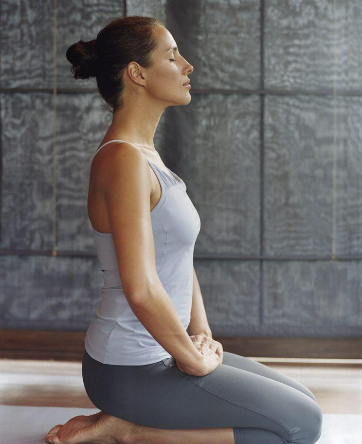 A woman sits on the floor in a yoga pose, eyes closed.