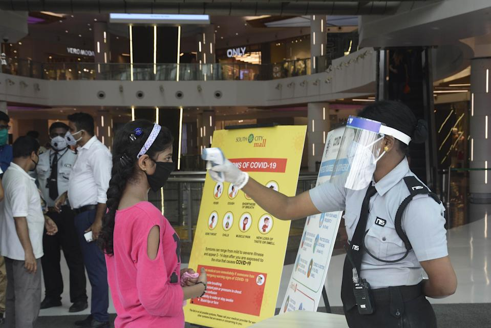 KOLKATA, INDIA - JUNE 8: A security guard thermal screening people at South City Mall as it opens to the public after lockdown relaxations, on June 8, 2020 in Kolkata, India. (Photo by Samir Jana/Hindustan Times via Getty Images)