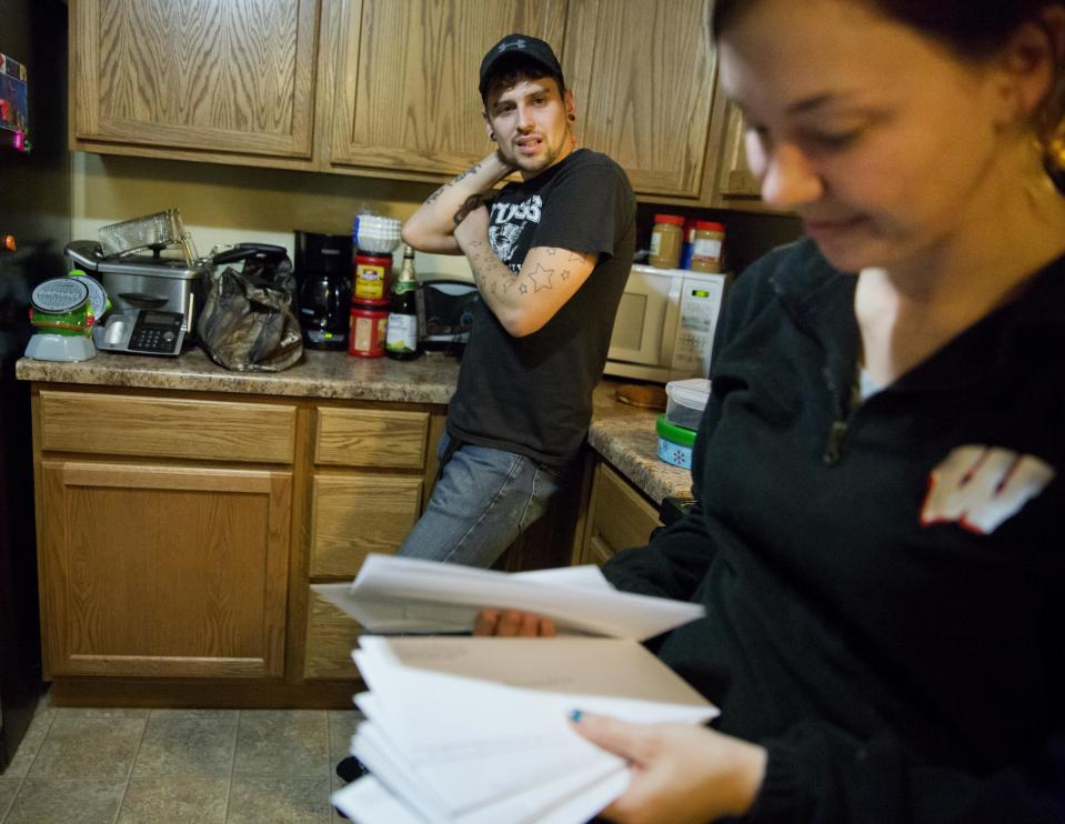 Kreig Holt, left, looks on as his wife, Lydia, flips through envelopes, each containing money for the each of the monthly bills they have to pay. (Photo: AP Photo/David Goldman)