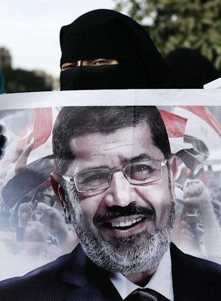 A Supporter of Egyptian President Mohammed Morsi, seen in the banner, chants slogans during a demonstration in Cairo, Egypt, Tuesday, Dec. 11, 2012. Islamists led by Morsi's Muslim Brotherhood group have called a demonstration to back the president's decision to hold a referendum on the new constitution on December 15. Opposition groups have rejected the constitution as undemocratic and want the vote canceled. (AP Photo/Hassan Ammar)