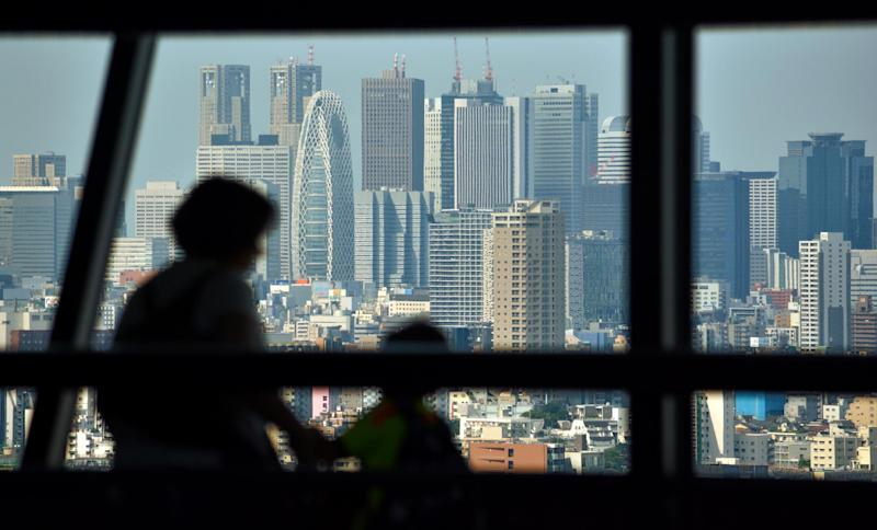 Visitors at an observatory floor look towards the skyline of Tokyo's commercial district of Shinjuku, August 13, 2014