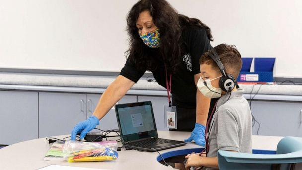 PHOTO:An instructional assistant helps a student as in-person learning resumes with restrictions in place to prevent the spread of coronavirus disease (COVID-19) at Wilson Primary School in Phoenix, Ariz., Aug. 17, 2020. (Cheney Orr/Reuters)