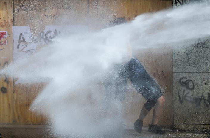 A demonstrator is sprayed by security forces with a water cannon during a protest against Chile's state economic model in Santiago, Chile on Oct. 23, 2019. (Photo: Ivan Alvarado/Reuters)