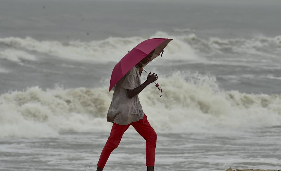 A man walks along a shore before the landfall of Cyclone Nivar, at Marina Beach in Chennai, Tuesday, 24 November, 2020.