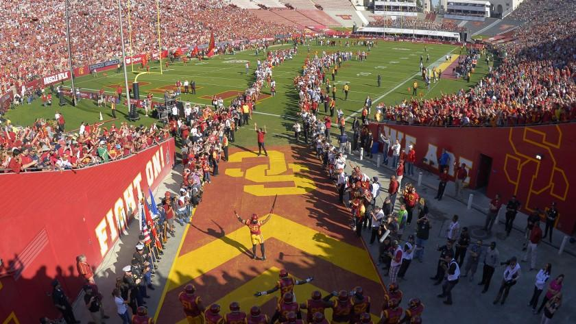 USC football players run onto the field at the Coliseum before a game against Notre Dame on Nov. 29.