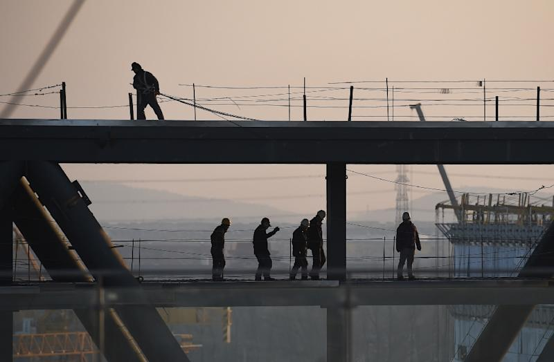Construction workers walk on the roof of the still-under-construction building in Beijing on December 17, 2014