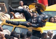 Cap executes an acrobatic maneuver across the top of a car. This scene appears to be set in Africa (some of the extras are dressed in traditional garb and one in the top left corner is carrying a basket on her head) — most likely Wakanda, the fictional country ruled by T'Challa, aka Black Panther.