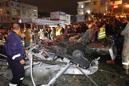 Civil defence members, Lebanese army soldiers and policemen inspect the wreckage of a van at the site of an explosion in Choueifat, south of the capital