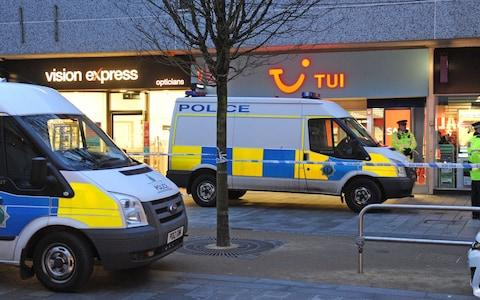 Police outside a travel agents in Southport where woman was attacked and was taken to hospital, where she later died from her injuries - Credit: PA