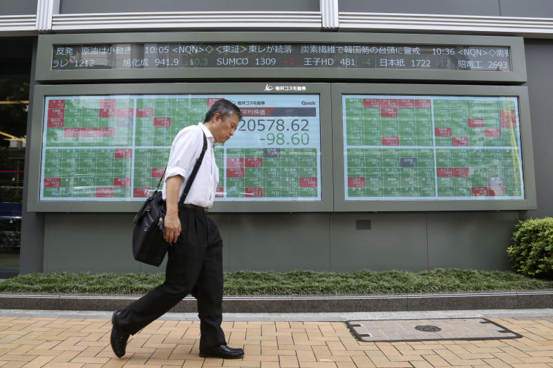 A man walks by an electronic stock board of a securities firm in Tokyo, Wednesday, Aug. 21, 2019. Asia stock markets followed Wall Street lower Wednesday as investors looked ahead to a speech by the Federal Reserve chairman for signs of possible plans for more U.S. interest rate cuts. (AP Photo/Koji Sasahara)
