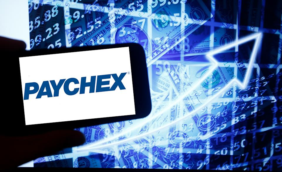 The logo of Paychex is seen on a screen of a smartphone next to a screen with an illustration of the stock market. Paychex is listed in Nasdaq. The Nasdaq is the second-largest stock exchange in the world after the New York Stock Exchange. (Photo by Alexander Pohl/NurPhoto via Getty Images)