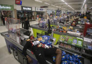 Jonata Anjo lies on a checkout counter at a Carrefour supermarket during a protest against the murder of Black man Joao Alberto Silveira Freitas at a different Carrefour supermarket the night before, on Brazil's National Black Consciousness Day in Rio de Janeiro, Brazil, Friday, Nov. 20, 2020. Freitas died after being beaten by supermarket security guards in the southern Brazilian city of Porto Alegre, sparking outrage as videos of the incident circulated on social media. (AP Photo/Bruna Prado)