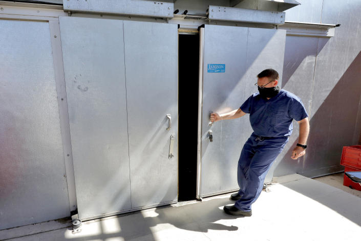 FILE - In this July 29, 2020, file photo, Pima County Medical Examiner Dr. Greg Hess opens the overflow body storage cooler at the medical examiner's office in Tucson, Ariz. After a record hot and dry summer, more deaths among border-crossers have been documented in Arizona's desert and mountains. The office of Dr. Hess works with the nonprofit Humane Borders in Tucson to map the recoveries of migrants who die along Arizona's entire border region. (AP Photo/Matt York, File)